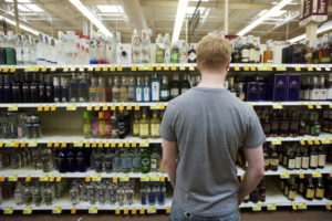 Man choosing duty free drinks in Andorran supermarket